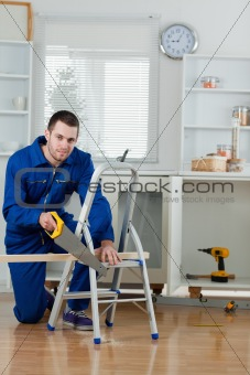 Portrait of a handyman cutting a wooden board