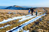 Family walk on autumn  mountain plateau with first winter snow