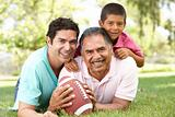 Grandfather With Son And Grandson In Park With American Football