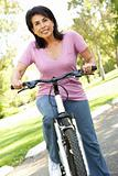Senior Woman Riding Bike In Park