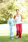 Mother And Daughter Exercising In Park
