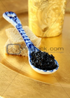 Black caviar in spoon on gold background