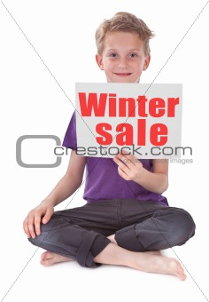boy holding white page with winter sale word
