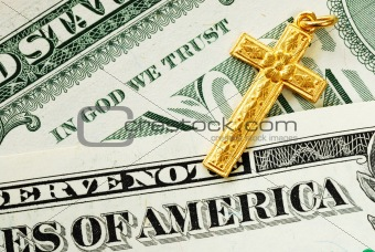A golden cross on the dollar bills concept of In God We Trust