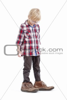 little boy wearing his father«s shoes - isolated on white