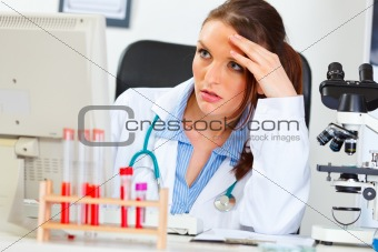 Concentrated doctor woman sitting in office and working on computer