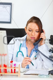 Doctor woman sitting in office and making phone call
