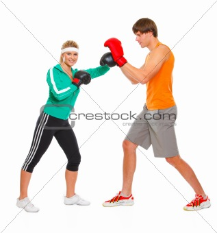 Fitness girl training boxing with help of personal trainer isolated on white