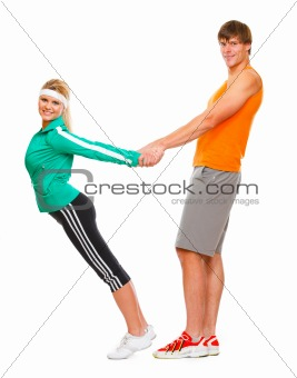 Slim young woman and male athlete having fun isolated on white