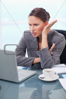 Portrait of an angry businesswoman working with a notebook