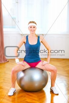 Slim girl in sportswear sitting on fitness ball