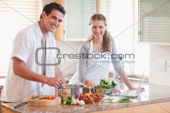 Couple using notebook to look up recipe