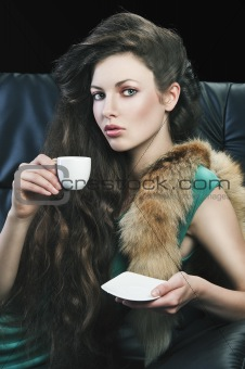 young elegant girl in green with cup, she is bringigng the cup t