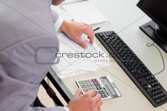 Above view of businessman using table calculator