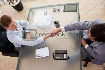 Above view of consultant shaking hands with customer