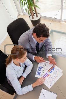 Above view of consultant analyzing diagram with her client