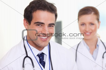 Smiling assistant doctors standing next to each other