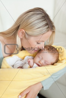 Affectionate mother kissing her sleeping baby in her arms
