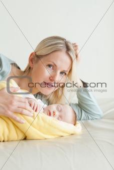Mom lying next to her sleeping baby