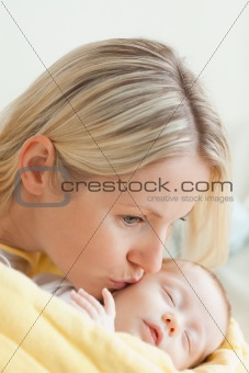 Affectionate mother kissing her sleeping baby's cheek