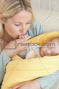Close up of mother kissing her baby's hand