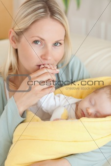 Close up of affectionate mother kissing her baby's hand