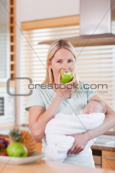 Mother with newborn on her arms having an apple