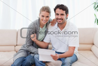 Delighted couple reading a letter