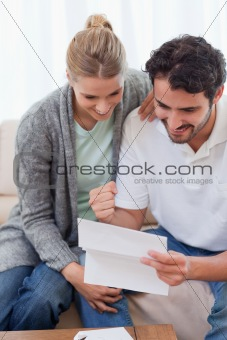 Portrait of a delighted couple reading a letter