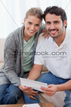 Portrait of a smiling couple reading a letter