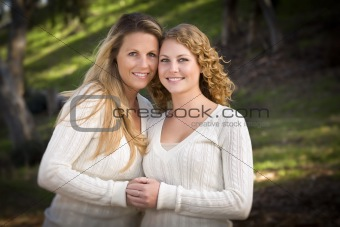 Pretty Mother and Daughter Portrait Hugging in the Park on a Fall Day.