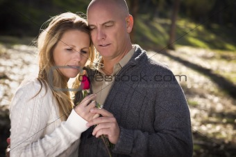 Attractive Young Couple Wearing Sweaters with a Rose in the Park.