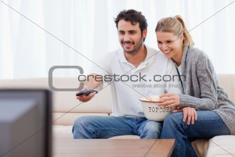 Smiling couple watching TV while eating popcorn