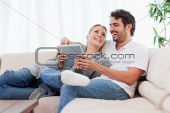 Delighted couple using a tablet computer