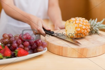 Close up of feminine hands slicing a pineapple
