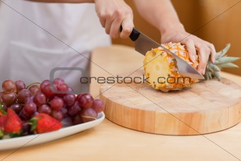 Close up of young feminine hands slicing a pineapple
