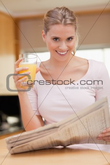 Portrait of a woman reading the news while drinking juice