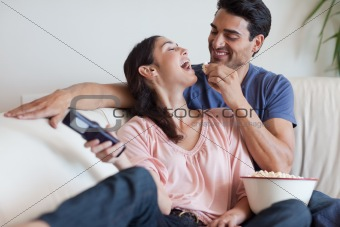 Playful couple watching TV while eating popcorn