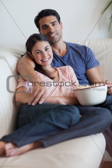 Portrait of a smiling couple watching television while eating popcorn