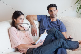 Woman reading a book while her boyfriend is watching television