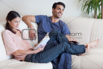 Woman reading a book while her husband is watching television