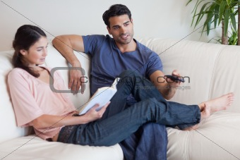 Woman reading a book while her fiance is watching television