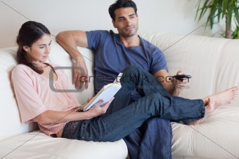 Woman reading a book while her fiance is watching TV