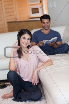 Portrait of a young woman listening to music while her boyfriend is reading a book