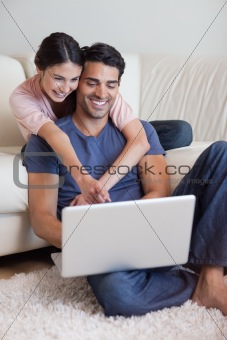 Portrait of a charming couple using a laptop
