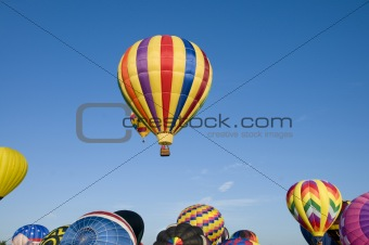 Hot-air balloons ascending over inflating ones