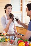Portrait of a young couple having a glass of wine while cooking