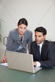 Portrait of sales persons working with a notebook