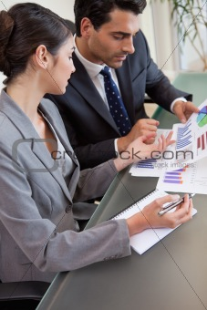 Portrait of sales persons studying graphs