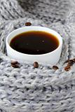 coffee in white cup wrapped in a gray scarf